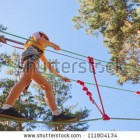 stock-photo-image-of-a-small-girl-having-her-time-in-the-children-s-rope-park-in-the-forest-111804134